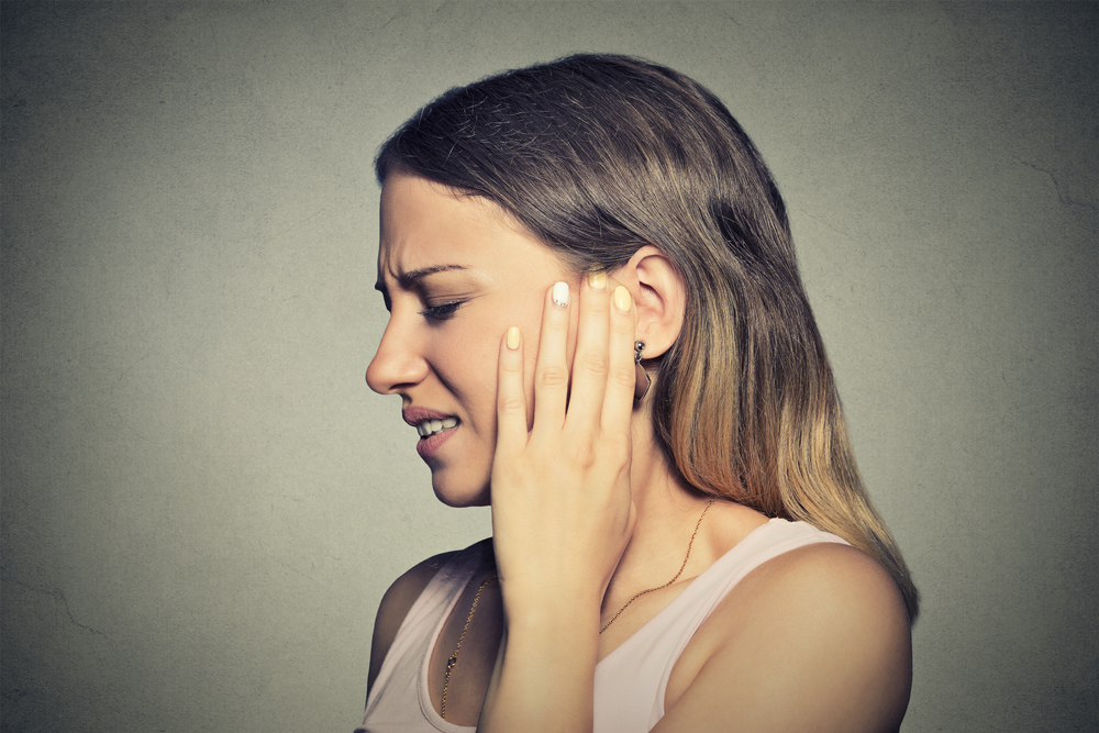 woman holing her jaw in pain from TMJ